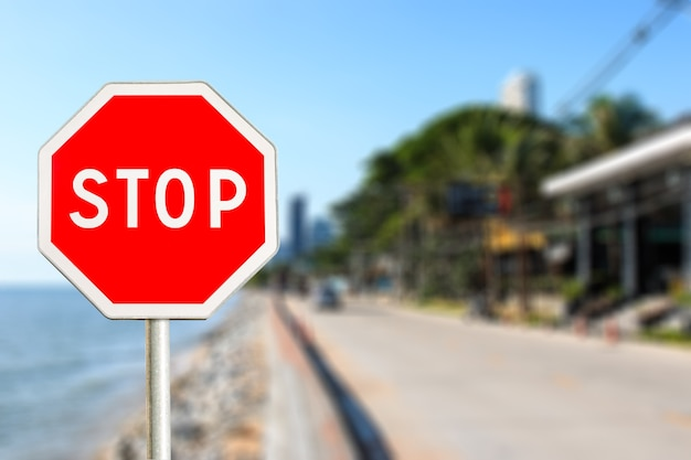 Stop sign by the city road near the sea