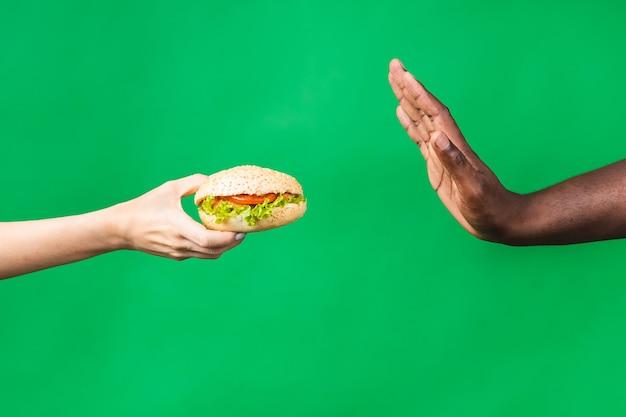 정지 신호. 녹색 배경 위에 격리된 건강에 해로운 햄버거를 거부하는 아프리카계 미국인 흑인 남성의 클로즈업 이미지.