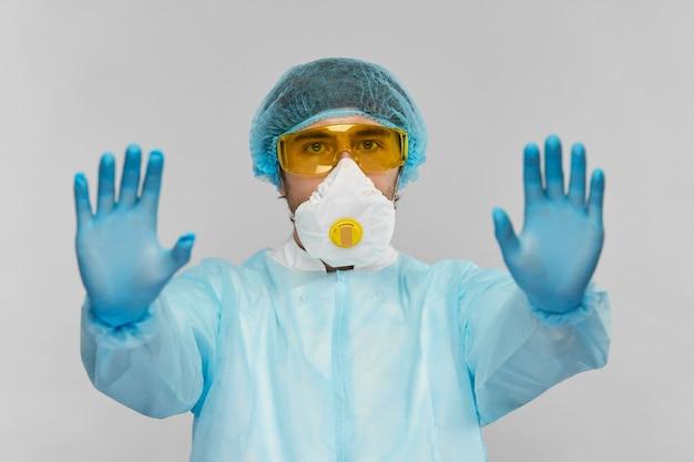 灰色で隔離されたバイオハザード保護衣装で医療科学者からの一時停止の標識