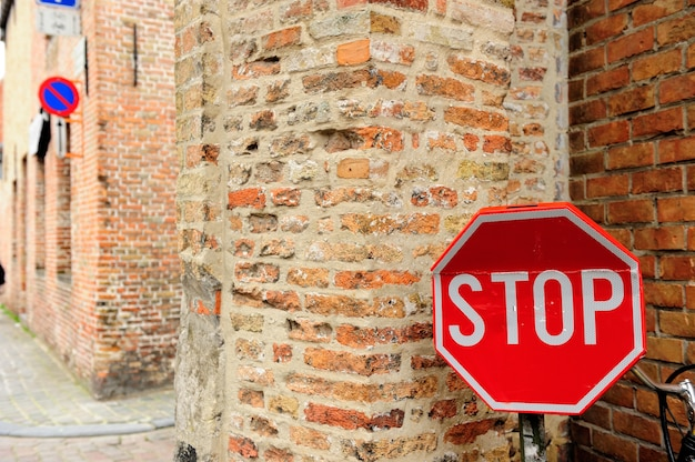 Stop sign in front of old brick wall in the small town