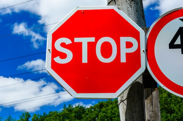 Stop sign on a post at roadside against blue sky