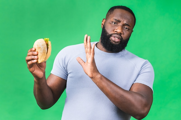 Знак стоп. молодой афро-американский черный человек ест гамбургер, изолированные на зеленом фоне. концепция диеты.
