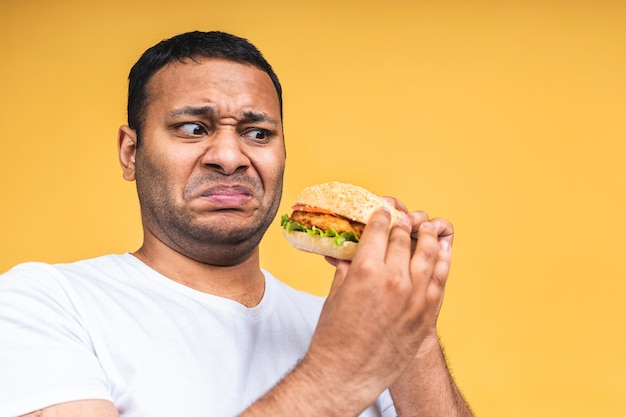 Знак стоп. молодой афро-американских индейцев черный человек ест гамбургер, изолированные на желтом фоне. концепция диеты.