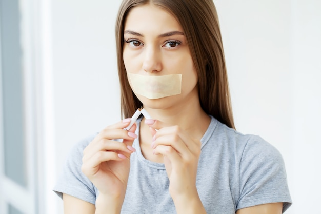 금연, 입이 봉인 된 젊은 여성이 건강에 미치는 흡연의 유해한 영향에 주목