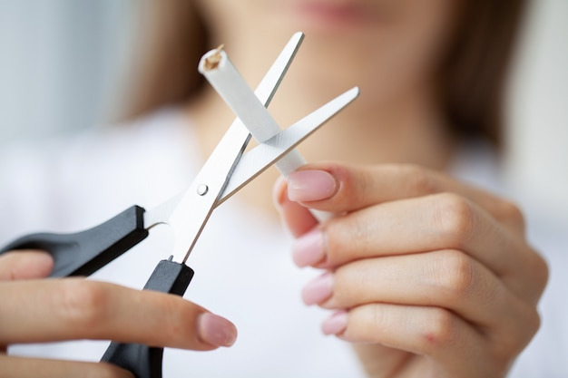 Бросить курить, крупный план женщины, ломающей сигарету