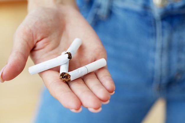 Бросить курить, крупным планом женщина держит сломанную сигарету