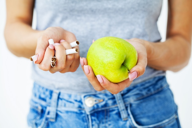 Stop smoking, close up of woman holding broken cigarettes and green appleapple