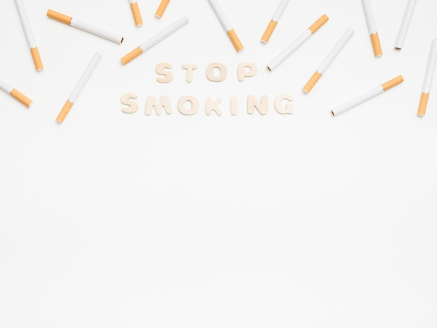 白い背景の上のタバコとメッセージを停止します。