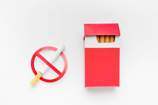 Stop smoking sign beside pack of cigarettes