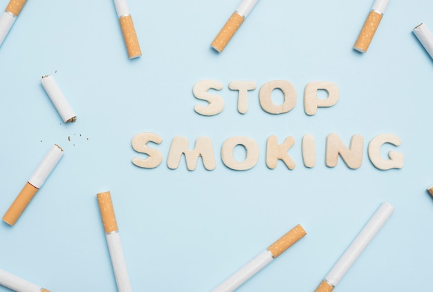 Stop smoking text with cigarettes on blue backdrop