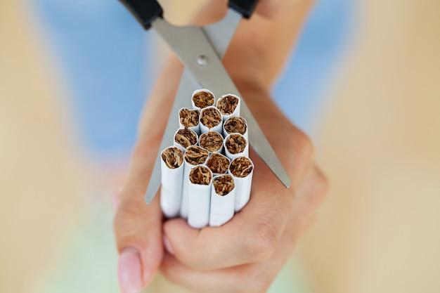담배를 끊으십시오, 어린 소녀는 손에 담배를 자릅니다.