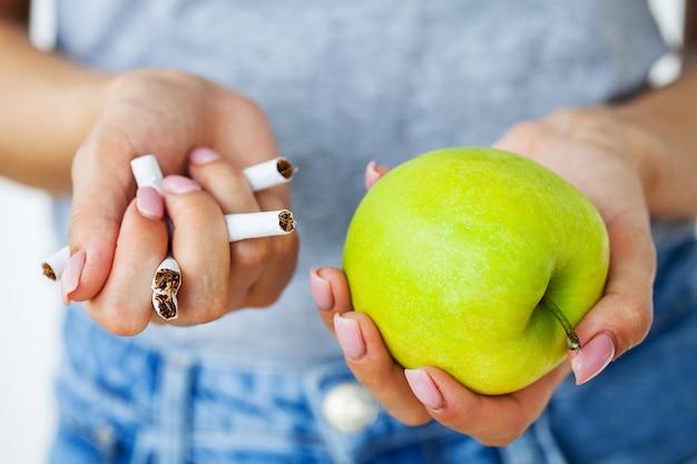 담배를 끊으십시오, 어린 소녀가 부러진 담배와 녹색 사과를 손에 들고 있습니다.