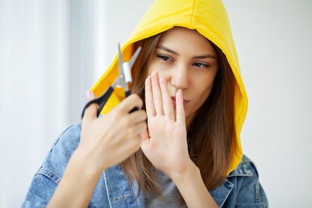 담배를 끊으십시오. 젊은 여성이 가위로 담배를 자릅니다.