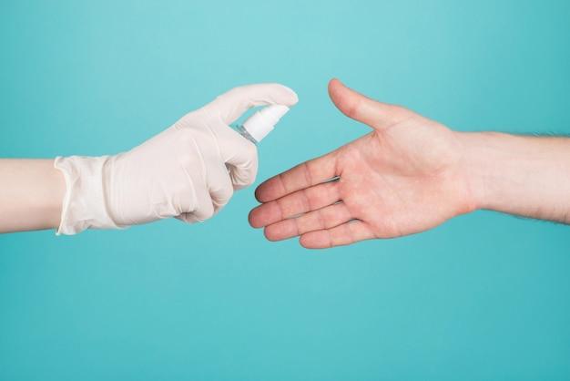 Прекратить распространение концепции пациента с коронавирусом. обрезанное фото крупным планом женщины в перчатках распыляет дезинфицирующее средство на мужской руке, изолированной на синем бирюзовом фоне