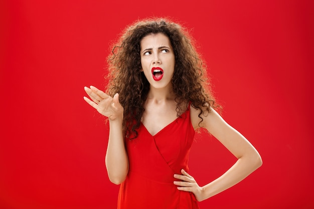 Stop talking you making me sick. displeased and arrogant picky dark-haired woman with curly hairstyle saying blah-blah turning away from annoying person rolling eyes up and frowning from aversion.