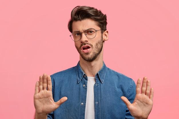 やめて、それで十分です!不機嫌そうな無精ひげを生やした若い男のスタジオショットは、停止ジェスチャーを行い、嫌いな顔を眉をひそめ、拒否を示しています