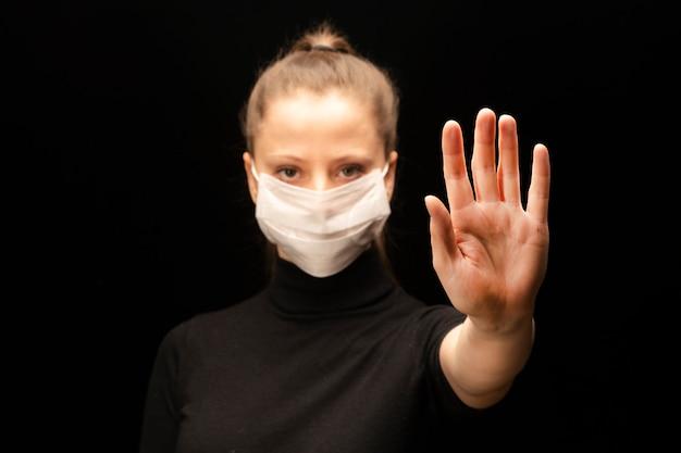 コロナウイルスを止めます。少女の手は、感染症からの保護のシンボル、または家にいるようにという呼びかけとして、一時停止の標識を象徴しています。壁のぼかしの女の子。