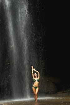 순간을 중지합니다. 폭포 아래 서 있는 동안 수영복을 입고 카메라에 포즈를 취하는 쾌활한 여자