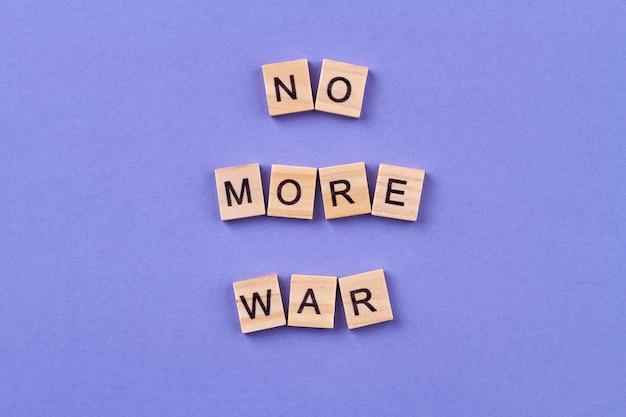 전쟁 개념을 중지하십시오. 인류와 평화에 대한 아이디어. 파란색 배경에 고립 된 편지와 함께 나무 큐브.