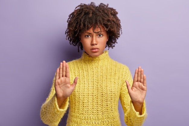 Stop this immediately. serious curly young woman shows palms in no gesture, has displeased facial expression, denies to help, talks about something forbidden, wears knitted jumper, stands indoor