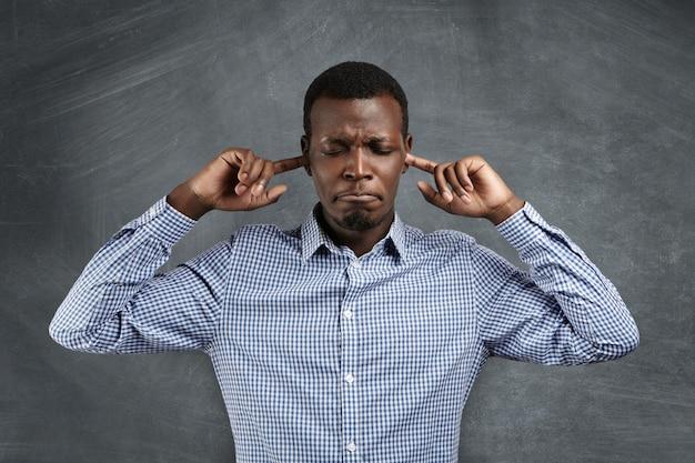 이 소리 멈춰! 그의 귀를 막고, 손가락으로 그들을 막고, 눈을 감고, 시끄러운 소리로 고통받는 동안 입술을 움켜 쥐고 셔츠에 분노하고 좌절 한 아프리카 남자의 초상화. 부정적인 감정