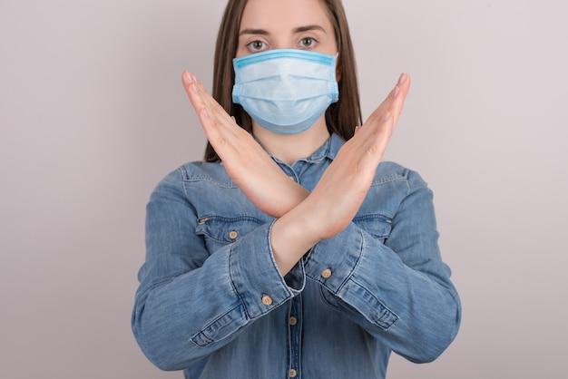 コロナウイルスの概念にとどまります。灰色の壁に隔離された手で一時停止のシンボルを作る深刻な女の子の写真を閉じる