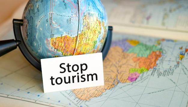 Остановка туризма в связи с кризисом и пандемией, прекращением полетов и туров для путешествий. текст в одной руке на фоне земного шара америки