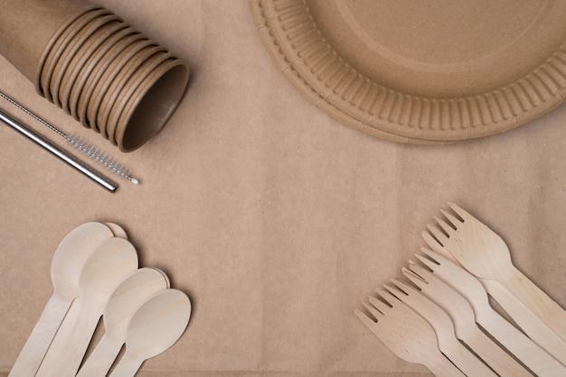 プラスチックの概念の使用をやめます。木製のカトラリー、紙コップとプレート、およびコーナーに配置された金属製のストローの俯瞰写真の上の上部は、クラフト紙の背景テーブルで隔離された中央を空にします