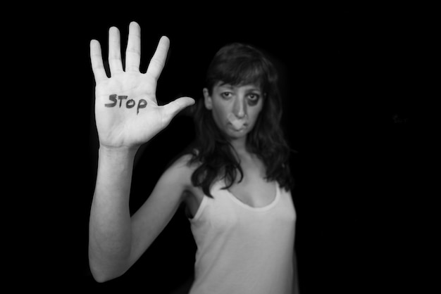 Stop violence against women. woman with mouth closed by patch and hand written stop