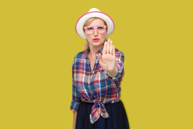 Stop or wait. portrait of angry or scared modern stylish mature woman in casual style with hat and eyeglasses standing with stop hand sign gesture. indoor studio shot isolated on yellow background.