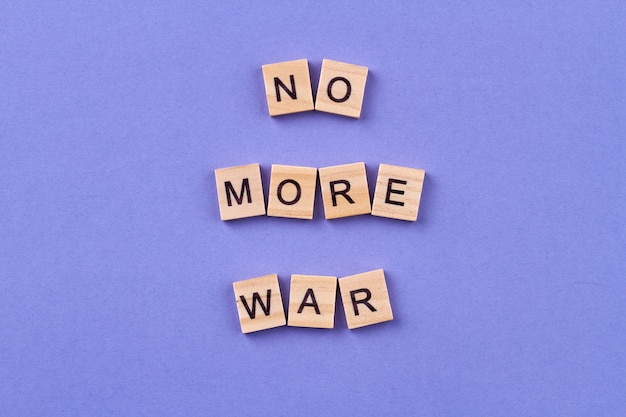 Stop the war concept. idea of humanity and peace. wooden cubes with letters isolated on blue background.