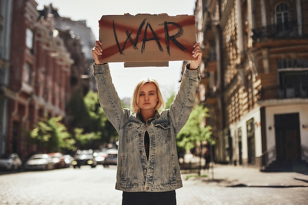 Stop war young confident female holding a signboard with word war strikethrough while standing on