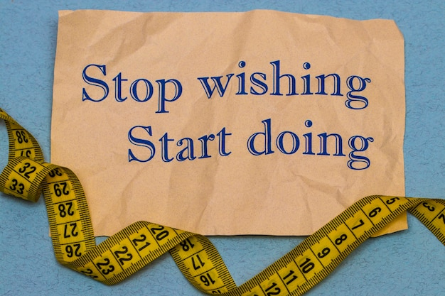 Stop wishing, start doing! motivational phrase on a sheet of paper with dumbbells and measuring tape on blue background