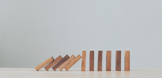 Stop wooden domino business crisis effect or risk protection concept
