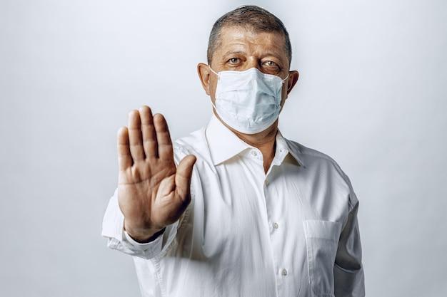Остановить мировую пандемию коронавируса. портрет мужчины в рубашке в защитной маске