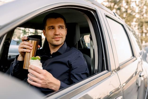 軽食をとるために立ち寄ります。男は車の中でおやつを食べ、コーヒーやお茶を飲みます。