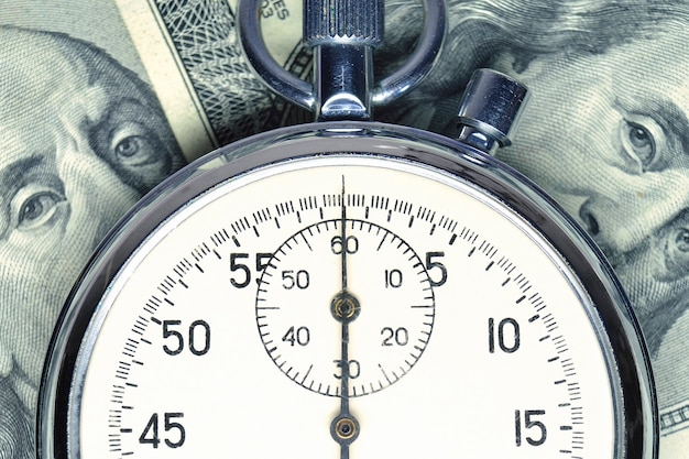 Stopwatch lays over us dollar banknotes