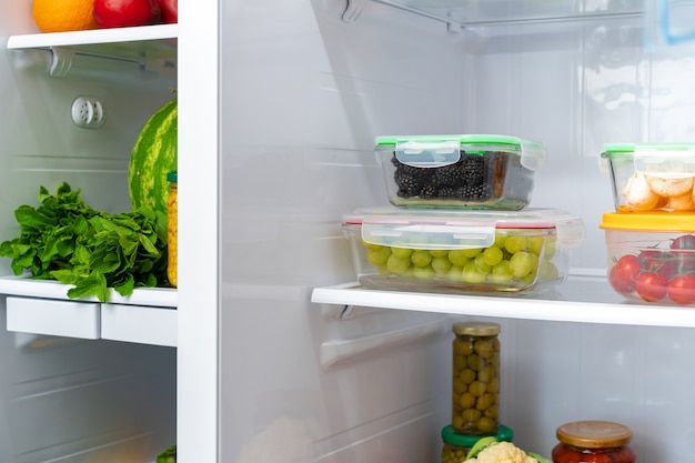 Storage containers with fresh food in a fridge close up