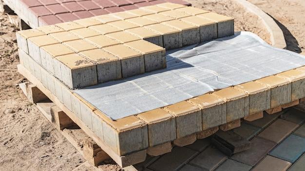 Хранение тротуарной плитки на поддонах на стройплощадке. готовая к установке бетонная тротуарная плитка. склад готовой продукции.