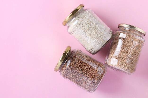 ガラスの瓶に米、そば、小麦の割りを保管。ピンクの背景の検疫隔離期間の危機食品ストック
