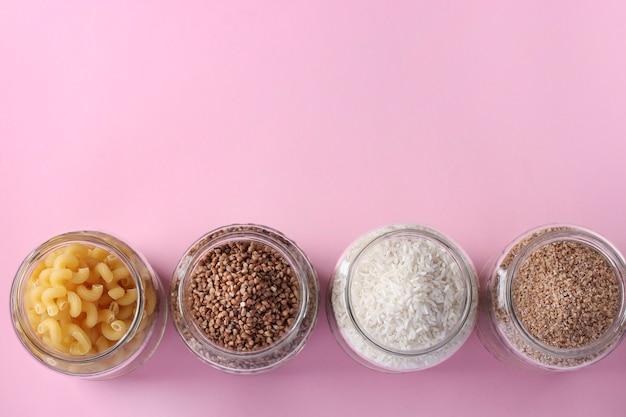 Хранение риса, гречки, пшеничной крупы и макарон в стеклянных банках. кризисные запасы продовольствия на период карантинной изоляции на розовой поверхности, вид сверху, место для текста