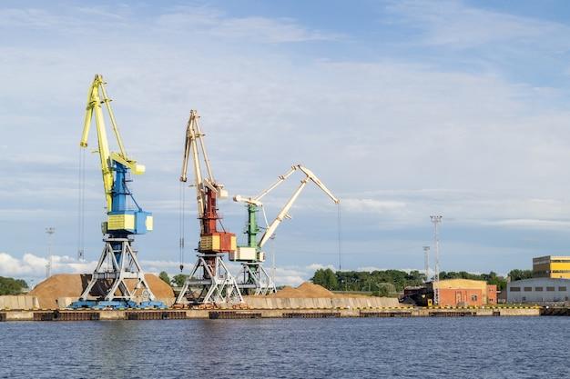 Склад, портовый кран, промышленная сцена. грузовые краны в терминале речного порта в вентспилсе