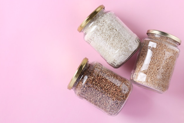 Storage of rice, buckwheat and wheat groats in glass jars. crisis food stock for quarantine isolation period on pink background