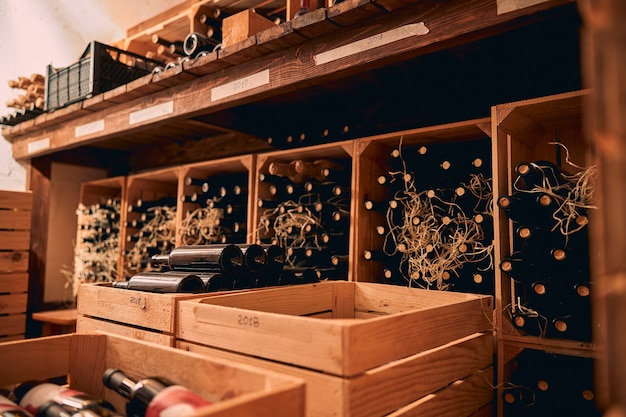 Storage room or wine cellar with bottles of alcoholic drink in wooden boxes and shelves with vintage year labels