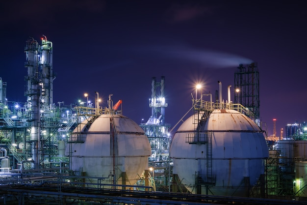 Storage sphere tanks in oil and gas refinery plant with night, glitter lighting of petrochemical plant, industrial plant with ultraviolet sky