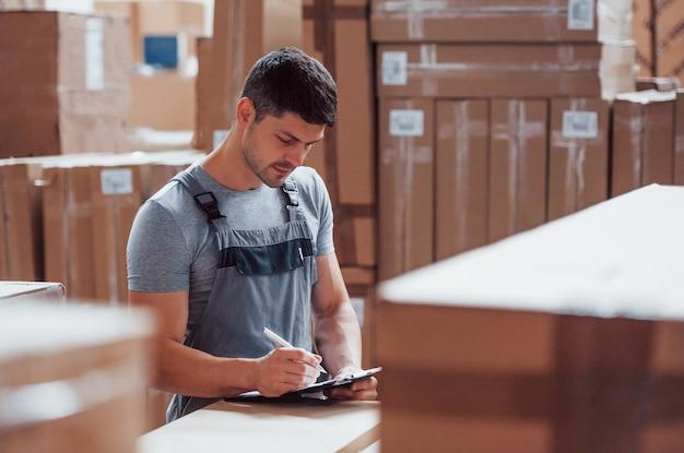 Работник склада в форме и блокнот в руках проверяет продукцию.