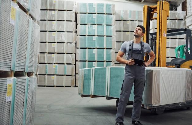 Работник склада в униформе и таблетке в руках проверяет производство.