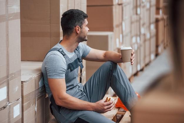 Работник склада сидит и отдыхает. ест бутерброд и пьет кофе.