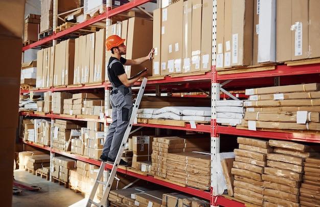 保管作業員は、制服を着たはしごの上に立ち、メモ帳を手にして、生産をチェックします。