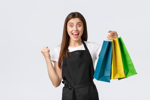 Сотрудник магазина в черном фартуке кулак нагнетает триумф и радуется, улыбаясь счастливой, держа заказ клиента, передавая сумки с купленными товарами в магазине, в котором она работает, на белом фоне